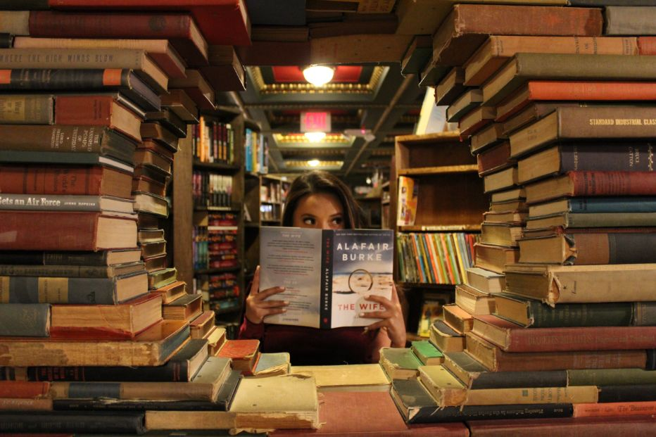 Girl hidden behind a pile of books in a library