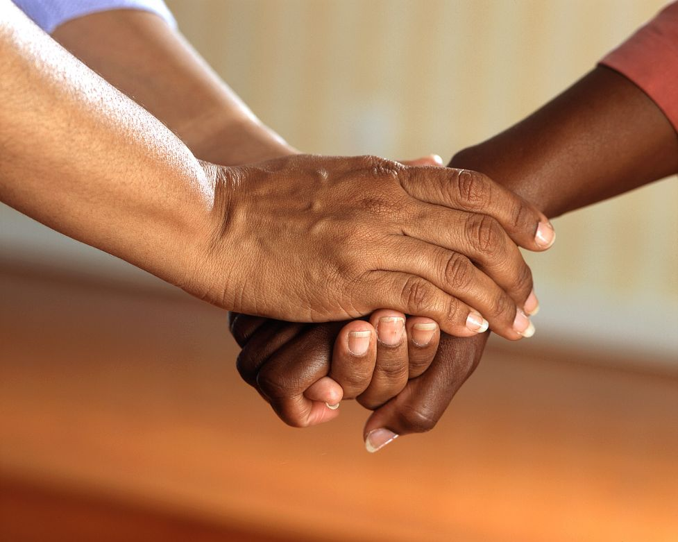 Two pairs of hands holding each other. Photo by Pixabay from Pexels.