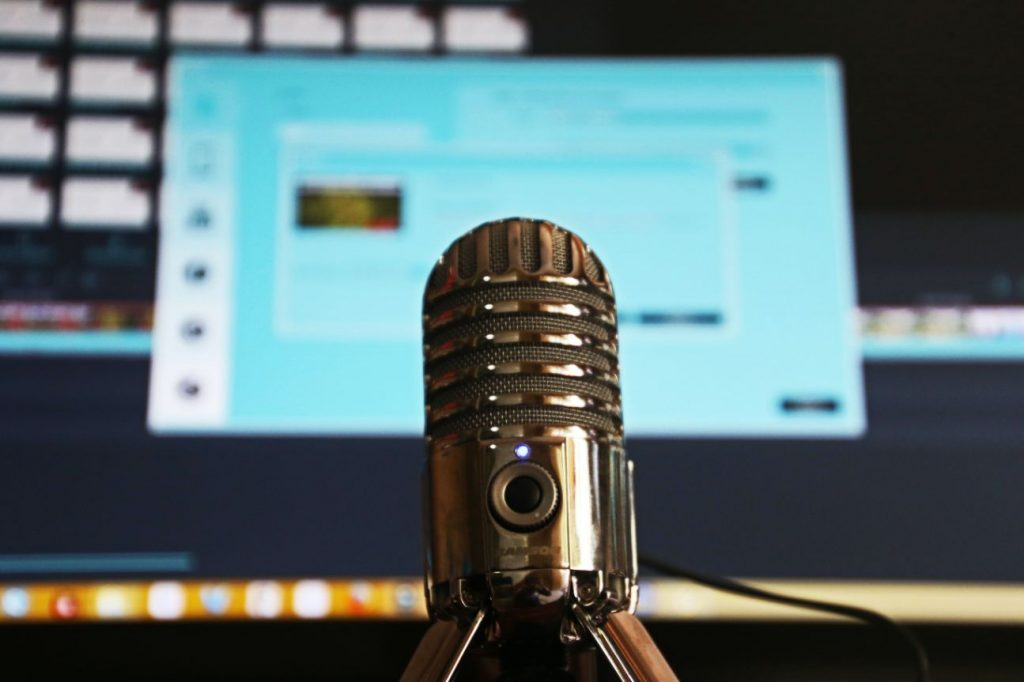 Microphone and computer screen ready to record a podcast.